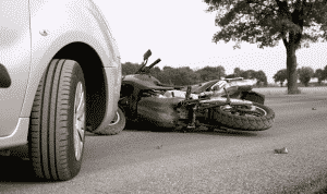 a car and motorbike in the road following a motorcycle accident
