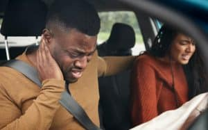 A man and woman experiencing symptoms of whiplash following a car accident
