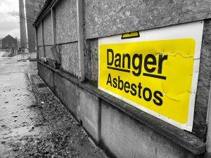Asbestos danger sign on derelict industrial building